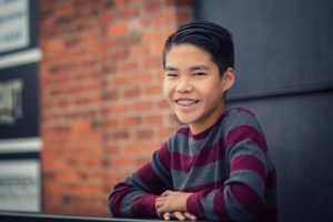 Happy smiling teenage asian boy with braces leaning over outdoor railing.