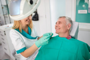 Female dentist strives to find closest color of dentures teeth to male patient